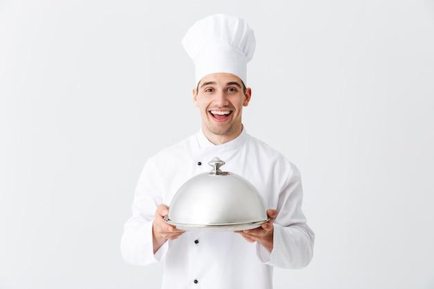 Podekscytowany kucharz mężczyzna ubrany w mundur gospodarstwa cloche na białym tle nad białą ścianą