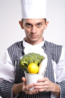 Podekscytowany kucharz mężczyzna ubrany w mundur trzyma wiadro warzyw na białym tle nad białym tle