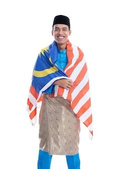 Podekscytowany malajski mężczyzna muzułmanin z flagą na białym tle