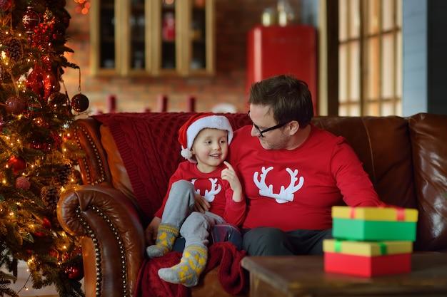 Podekscytowany mały chłopiec i jego ojciec siedzą na kanapie z prezentem świątecznym pod choinką w domu. portret szczęśliwy dzieciak w poranku bożonarodzeniowy.