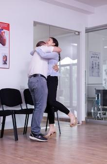 Podekscytowany mąż przytula żonę po otrzymaniu dobrych wieści od lekarza w szpitalnej poczekalni. szczęśliwa młoda para za dobry wynik kliniczny krzyczy w recepcji