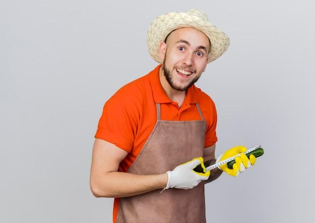 Podekscytowany męski ogrodnik w kapeluszu ogrodniczym mierzy ogórek centymetrem