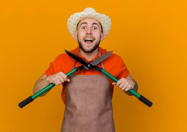Podekscytowany męski ogrodnik w kapeluszu ogrodniczym trzyma nożyce ogrodowe
