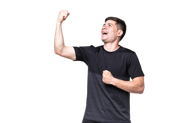 Podekscytowany mężczyzna fitness z gestem zwycięzcy na białej ścianie
