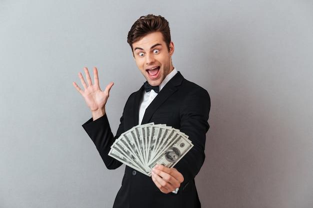 Podekscytowany mężczyzna krzyczy w oficjalnym garniturze, trzymając pieniądze.