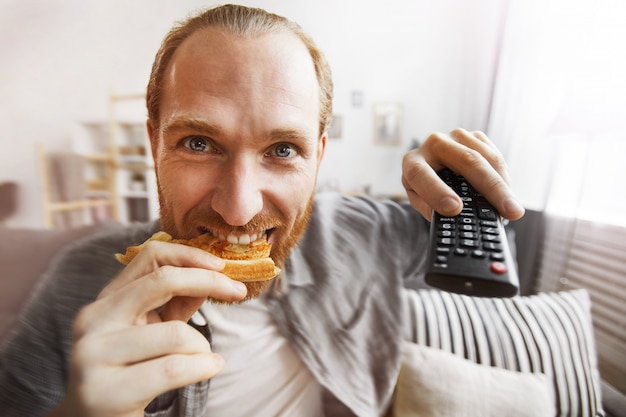 Podekscytowany mężczyzna ogląda telewizję w domu