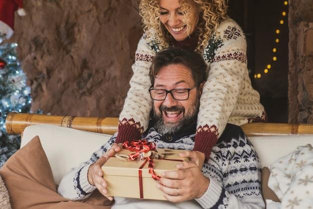 Podekscytowany mężczyzna otrzymuje prezent od żony w domu na święta