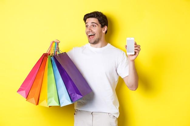 Podekscytowany mężczyzna pokazujący ekran smartfona i torby na zakupy, osiągający cel aplikacji, demonstrujący aplikację bankowości mobilnej, żółte tło.