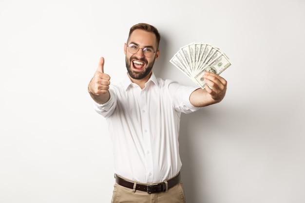 Podekscytowany mężczyzna pokazuje kciuki i pieniądze, zarabianie pieniędzy, stojąc na białym tle.