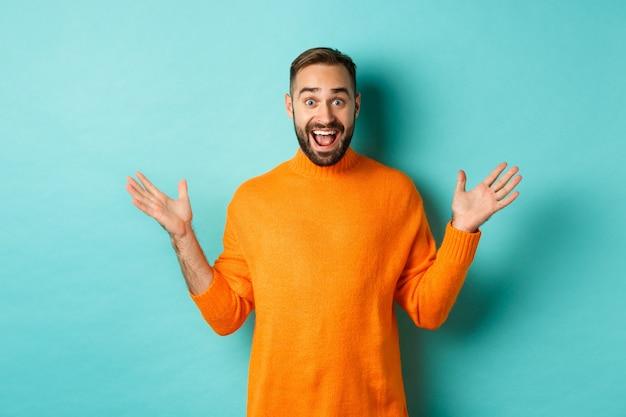 Podekscytowany mężczyzna reaguje na ofertę promocyjną, rozkłada ręce na boki i radośnie stając naprzeciw turkusu