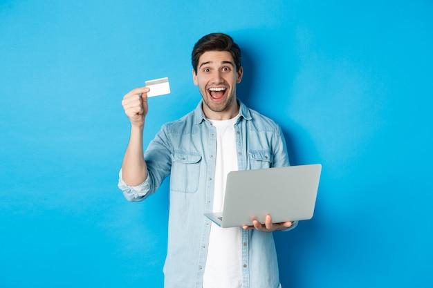 Podekscytowany mężczyzna robi zakupy online, pokazując kartę kredytową i trzymając laptopa, kupując w internecie, stojąc nad niebieską ścianą