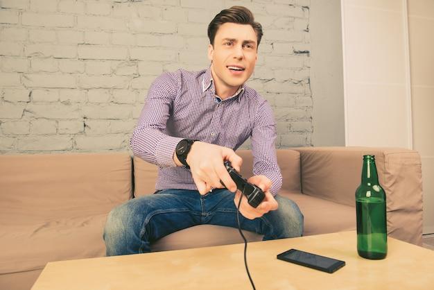 Podekscytowany mężczyzna siedzi na kanapie z butelką piwa i grając w gry wideo