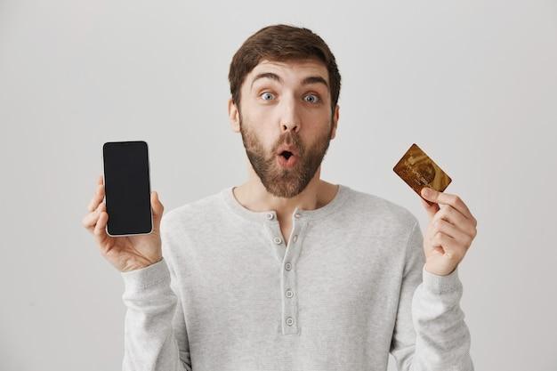 Podekscytowany mężczyzna składający zamówienie online, pokazujący kartę kredytową i ekran telefonu komórkowego