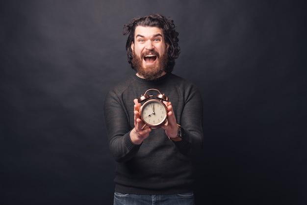 Podekscytowany mężczyzna trzyma mały zegar i jednocześnie jest zestresowany