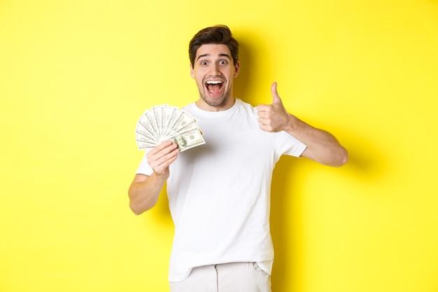 Podekscytowany mężczyzna trzymający pieniądze, pokazujący kciuk do góry z aprobatą, dostał kredyt lub pożyczkę, stojąc nad żółtą ścianą