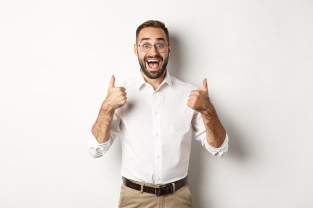 Podekscytowany mężczyzna w okularach pokazujący kciuki do góry i wyglądający na zdumionego, zgadza się i aprobuje coś wspaniałego