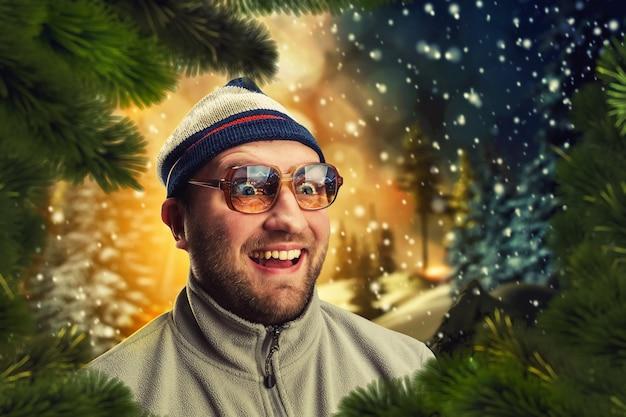 Podekscytowany mężczyzna w zimowy wieczór w pobliżu jodeł