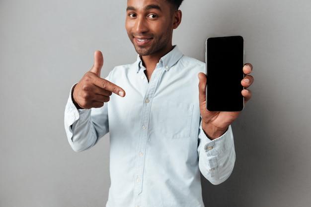 Podekscytowany mężczyzna wskazując palcem na pusty ekran telefonu komórkowego