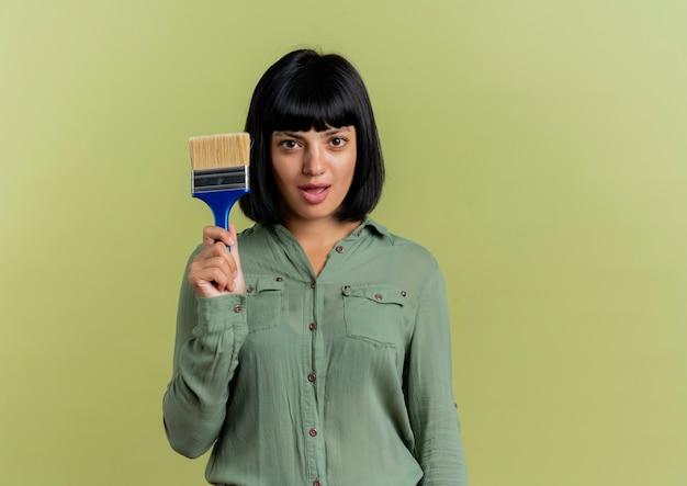Podekscytowany młoda brunetka kaukaski dziewczyna trzyma pędzel i patrzy na aparat na białym tle na oliwkowym tle z miejsca na kopię