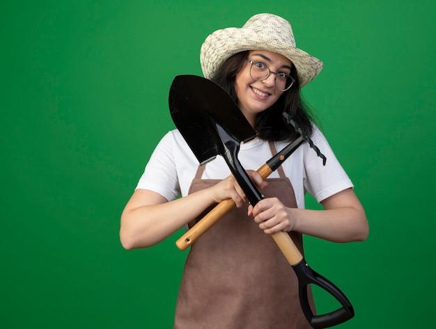 Podekscytowany młoda brunetka ogrodniczka w okularach optycznych i mundurze w kapeluszu ogrodniczym trzyma łopatę i grabie na białym tle na zielonej ścianie