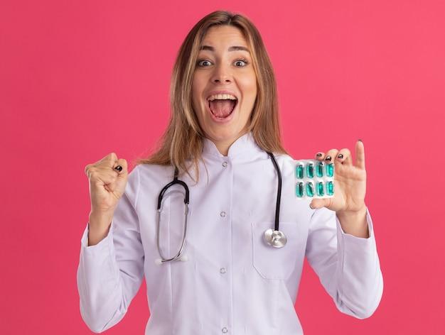 Podekscytowany młoda kobieta lekarz ubrana w szlafrok medyczny ze stetoskopem trzymając pigułki pokazujące tak gest na białym tle na różowej ścianie