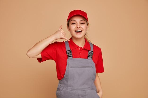 Podekscytowany młoda kobieta pracownik budowlany na sobie mundur i czapkę, trzymając rękę w kieszeni, robi gest połączenia