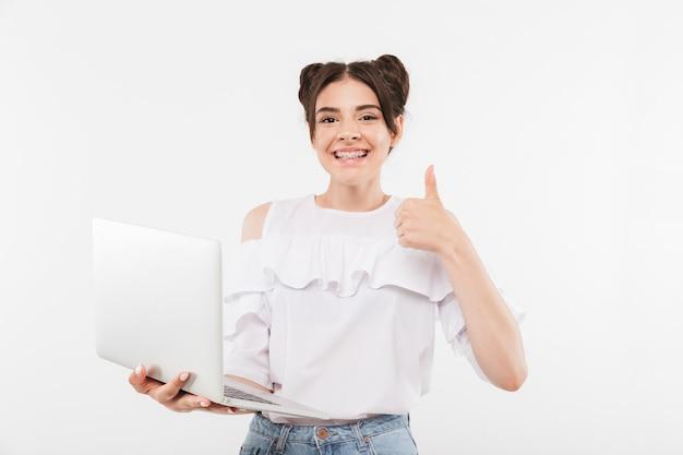 Podekscytowany młoda kobieta z podwójną bułeczkami fryzurę i szelki na zęby trzymając laptopa i pokazując kciuk do góry, na białym tle
