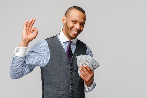 Podekscytowany młody afroamerykanin trzyma pieniądze w gotówce i pokazuje znak ok na jasnoszarej ścianie