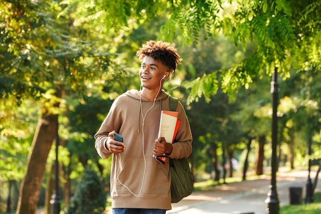Podekscytowany młody afrykanin z plecakiem chodzącym
