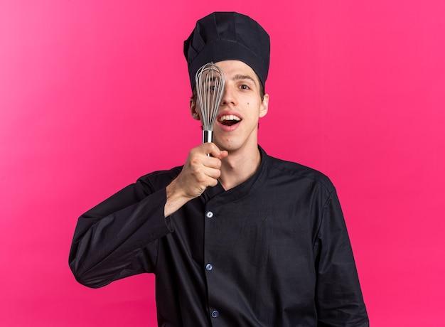 Podekscytowany młody blond kucharz w mundurze szefa kuchni i czapce, patrząc na kamerę zakrywającą połowę twarzy trzepaczką odizolowaną na różowej ścianie