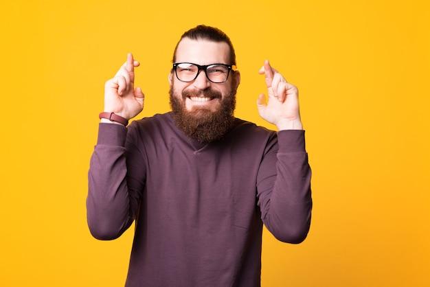 Podekscytowany młody brodacz w okularach ma nadzieję, że jego marzenia spełnią się przy białej ścianie