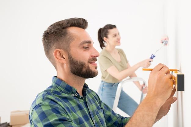 Podekscytowany młody brodaty mężczyzna stojący na drabinie i wkręcający śrubę w ścianę podczas wieszania obrazu na ścianie z żoną