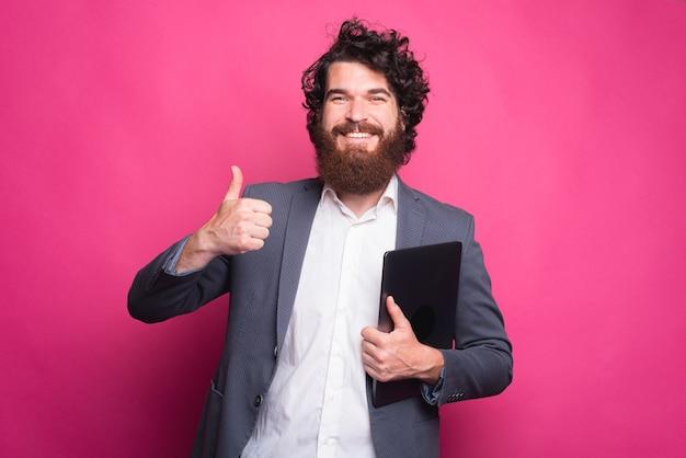 Podekscytowany młody brodaty mężczyzna w garniturze pokazuje kciuk do góry i trzyma laptopa