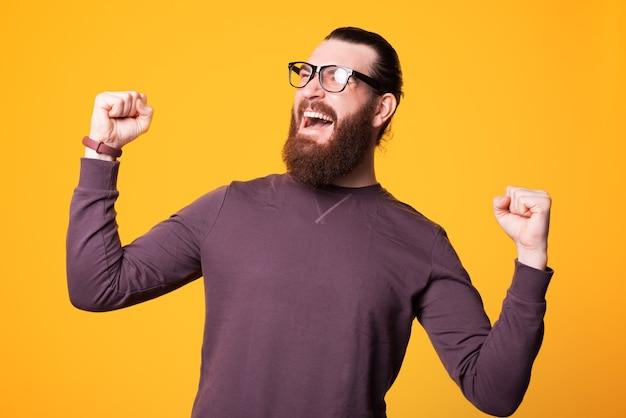 Podekscytowany młody brodaty mężczyzna w okularach krzyczy radość i trzyma obie ręce w górze