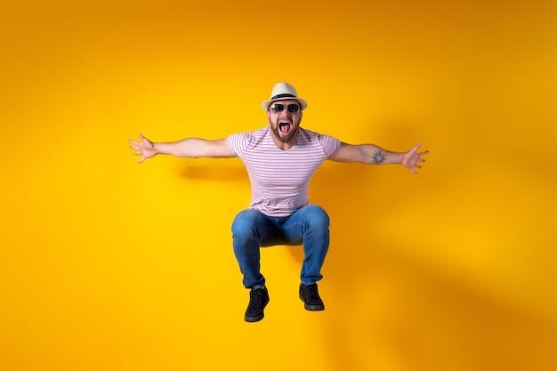Podekscytowany młody brodaty sportowy facet w kapeluszu i okularach przeciwsłonecznych skacze bardzo emocjonalnie odizolowany na żółto
