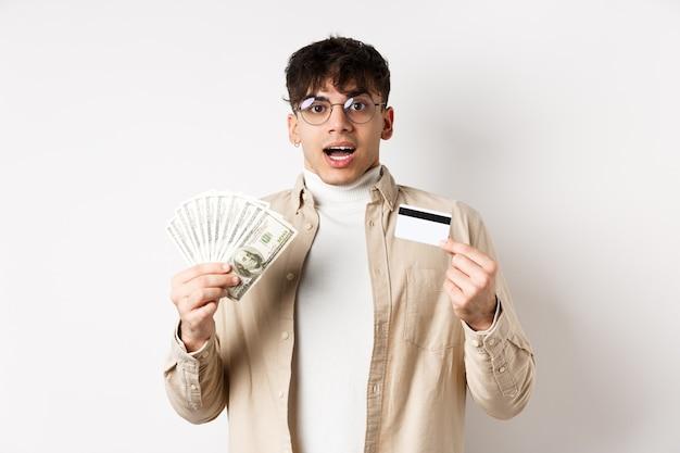 Podekscytowany młody chłopak pokazuje dolary i kartę kredytową, zarabia pieniądze i wygląda na zdumionego, stojąc na białej ścianie.