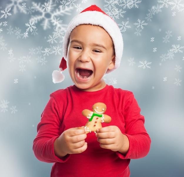 Podekscytowany młody chłopak świętować boże narodzenie z piernika