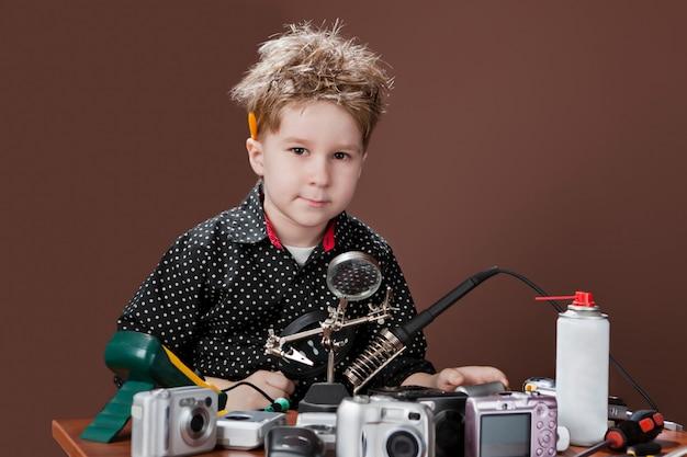 Podekscytowany młody chłopak uśmiecha się i naprawia aparaty fotograficzne.