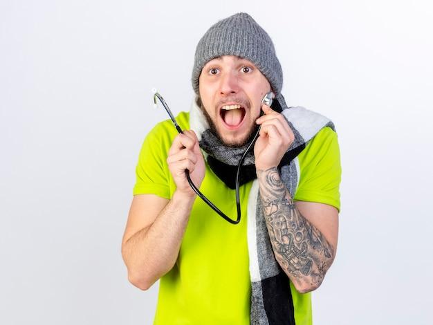 Podekscytowany młody chory człowiek ubrany w czapkę zimową i szalik trzyma stetoskop na białym tle na białej ścianie