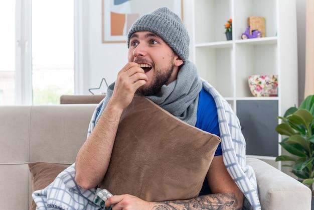 Podekscytowany młody chory człowiek ubrany w szalik i czapkę zimową zawiniętą w koc, siedzący na kanapie w salonie, trzymając poduszkę trzymając rękę na ustach patrząc na bok