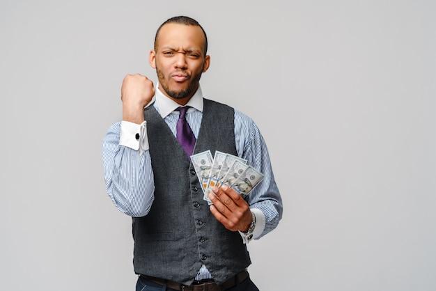 Podekscytowany młody człowiek afroamerykanin, trzymając pieniądze w gotówce i pokazując gest wygranej na jasnoszarej ścianie