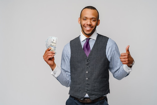Podekscytowany młody człowiek afroamerykanin, trzymając pieniądze w gotówce i pokazując kciuk w górę nad jasnoszarą ścianą