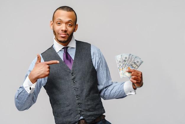 Podekscytowany młody człowiek afroamerykanin, trzymając pieniądze w gotówce i wskazuje na to na jasnoszarej ścianie