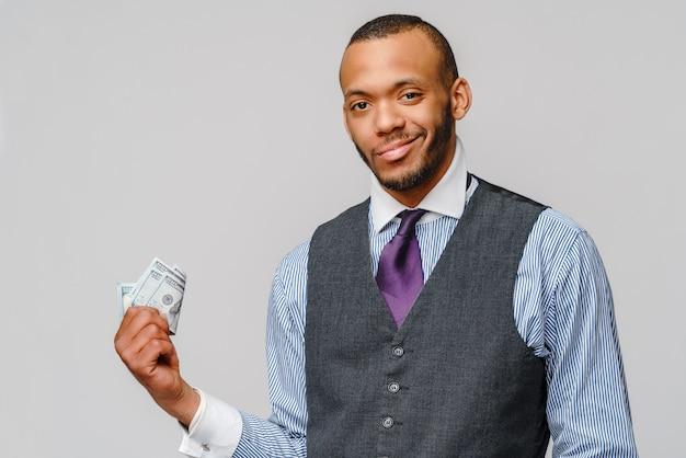 Podekscytowany młody człowiek afroamerykanin, trzymając pieniądze w gotówce nad jasnoszarą ścianą