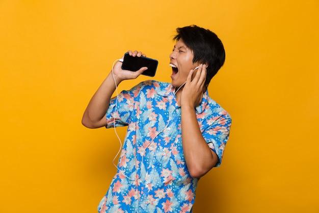 Podekscytowany młody człowiek azjatycki stojący na białym tle nad żółtą przestrzenią przy użyciu telefonu komórkowego słuchanie muzyki przez słuchawki.
