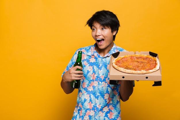Podekscytowany młody człowiek azjatycki stojący na białym tle nad żółtą przestrzenią trzymając pizzę do picia piwa.