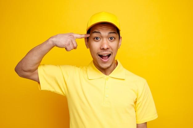 Podekscytowany młody człowiek dostawy czapkę i mundur robi gest myślenia