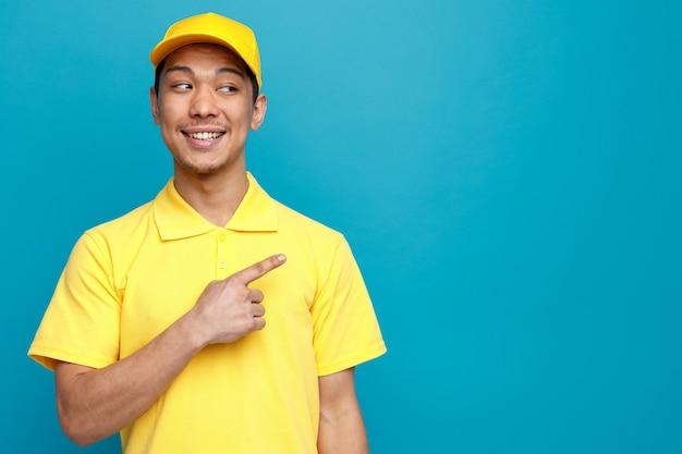 Podekscytowany młody człowiek dostawy ubrany w mundur i czapkę, patrząc i wskazując na bok
