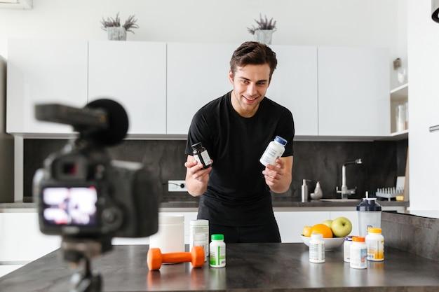 Podekscytowany młody człowiek filmujący swój odcinek blogu wideo