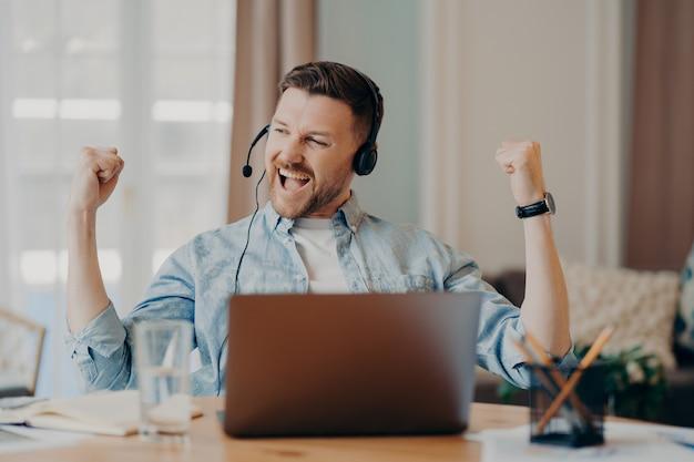 Podekscytowany młody człowiek freelancer zestaw słuchawkowy z mikrofonem świętujący sukces po ważnym spotkaniu online lub rozmowie kwalifikacyjnej, siedzący przy biurku w salonie w domu. zwycięska koncepcja zachowania